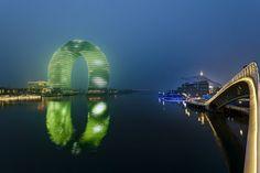 Un anello di congiunzione tra cielo e mare che di notte illumina la costa con la sua forma originale e tondeggiante nella città cinese Huzho...