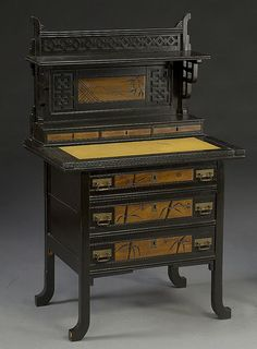 Anglo-Japanese cabinet constructed in 1880 with wood and an applied ebonised finish. The cabinets and writing surface are meant to emulate Japanese ink drawings.