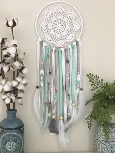 Medium Gray and Mint Dream Catcher. This is the perfect addition to a mint and gray boho nursery or bedroom. This dream catcher is made up of white, gray and mint green ribbons, lace and yarn. The addition of natural stones and feathers give this dream catcher depth. It features 3 unique hand painted feathers with boho designs. To customize any details visit www.shopwildcotton.com