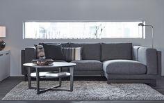 Ein Wohnzimmer mit 2er-Sofa und Récamiere mit dunkelgrauem Bezug und mit schwarzbraunem Couchtisch