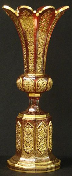 """This is a truly exceptional example of a Moser Bohemian art glass vase. The vase is a translucent cranberry glass made from 8 panels in a cylindrical array, flaring out in the center, then narrowing at the waist and flaring out againtowards the base. Each panel comes to a point with beveled edge.There are copious amounts of raised gilt enamel tracing intricate geometric patterns that cover each panel, a characteristic Moser trademark. Measures: 16"""" Tall X 6 7/8"""" Wide"""