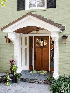 This suburban two-story needed an update, and the contractor-homeowners wanted the change to be subtle yet dramatic. See how a coat of gorgeous green paint and fetching fixtures gave the home exterior a brand-new look. Front Door Overhang, Front Door Entrance, Front Doors, Front Entrances, Exterior Makeover, Door Makeover, Portico Entry, Veranda Design, Front Porch Design