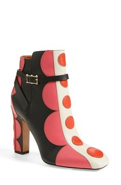 """Details & CareThe mod motif of this statement ankle bootie starts off with color-pop leather layers and finishes with squared-off shapes at the heel and toe.4"""" heel. Side-zip closu..."""