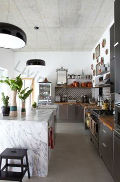 So much I love here...  marble waterfall island, graphic backsplash with the mix of warm wood countertops, open shelving, vintage mirrors and art hung above, huge farmhouse sink