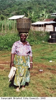 Photograph of a Bubi woman with a basket on her head, part of daily life in the village of Moka, on the Island of Bioko, Equatorial Guinea.