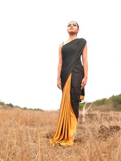 Embrace the beauty of contrasts with this Black and Gold Pleated Saree. This lovely drape can be pleated as and when you desire. The golden satin contrasts sharply against the soft grey and black makes for a truly striking saree.