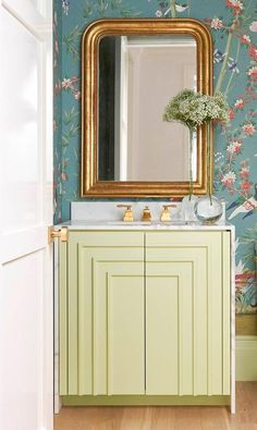 Gorgeous powder room boasts a wall clad in peacock blue chinoiserie wallpaper lined with a yellow art deco bath vanity accented with a white marble waterfall countertop placed beneath a gold french beaded mirror. Schumacher chinoiserie wallpaper powder room