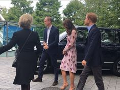 The Duchess teamed the floral frock with a pair of her favourite nude court shoesand clutch purse. Profile or side view of Catherine's lovely dress, hair worn long, walking with William and Harry.