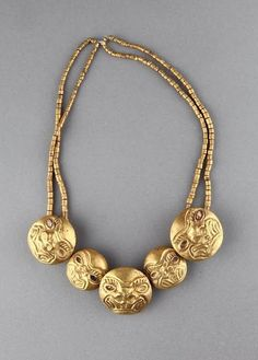 #Precolumbian  --  Gold Necklace  --  1-800 CE  --  Beads are etched with jaguar faces  --  No further reference provided.