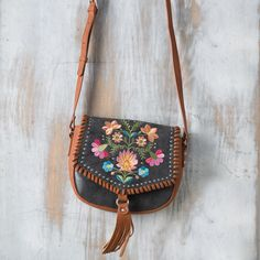 American West Wildflower Crossbody Bag- The eye-catching Wildflower Crossbody bag by American west is beautifully accented with a bright embroidered floral design and brown leather tassel detail. This crossbody bas is perfect for any cowgirl on the go