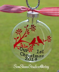 This glass ornament will make a beautiful keepsake for the new couple. You can be assured they will want to keep this ornament forever. Ornaments are glass and are 3-1/8 in diameter with a silver hanger. They are flattened (not round) similar to a pocket watch but thicker. Design includes birds on a branch, saying Our 1st Christmas and the year. You are welcome to choose any 2 colors of vinyl (see photo #3). If you want colors other than red and black please leave notes at checkout. If you…