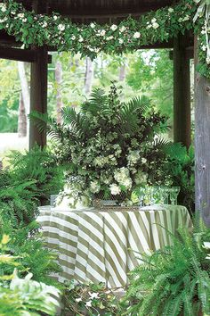 Adelicate cake nestled beneath a centerpiece of ferns, miniature roses and peonies.