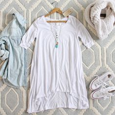 A cozy white knit jersey adorns this darling t-shirt tunic dress. Designed with a henley inspired button-up bust, 1/2 sleeves, high-low design, and a soft draped shape. Stretch fabric to ensure the perfect fit. Darling worn as a tunic or dress when paired with our Mercer Tank Dress underneath. Shown with our Tanner Denim Shirt & Turquoise Moon Necklace.  Color: White 60% cotton & 40% rayon Imported Hand wash cold        Small/Medium Medium/Large      Bust 37 39    Waist 36 38    Hips ...