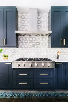 royal blue kitchen with cement tile back splash, brass hardware and stainless stovetop....so on trend