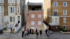 Artist Alex Chinneck has transformed an empty house in Cliftonville, Margate, to make it appear as if it is slowly sliding into the street.
