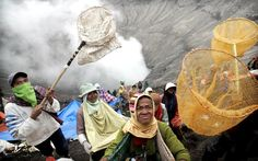July 26, 2013 Indonesian villagers use nets and sarongs to catch offerings thrown by Hindu worshippers into the crater of Mount Bromo during the Kasada festival in Probolinggo, East Java, Indonesia. Hindu worshipers from Tengger village gathered at the volcano for the Kasada annual festival where they throw offerings of rice, fruit, vegetables, livestock and money in to the volcano to express their gratitude to the Gods for good harvest and fortune.Picture: EPA