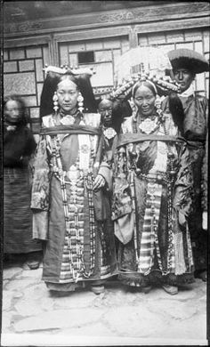 Photographer: Unknown, Collection: Sir Charles Bell, Date of Photo: 1904-1922 Region:Lhasa,. Two women in heavily ornamented dress. Behind are more women, less ornately dressed, and a man in fringed headgear. In the background a carved and painted wall or panel.