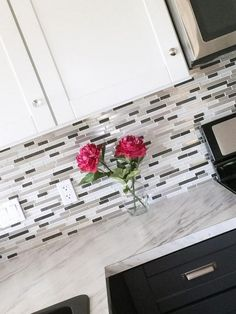 mosaic glass tile backsplash with metal in it white and gray marble countertops