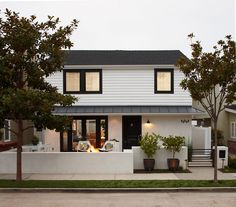 White and black home exterior design with semi-covered porch and black door and window moldings