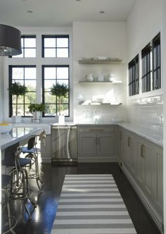 grey and white contemporary kitchen with no upper cabinets, double stacked windows, topiaries make it warm