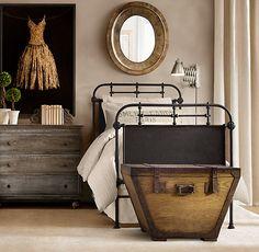 Metal bed, wooden chest, worn dresser, oval mirror