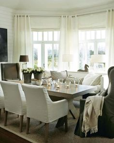 bright, cozy dining room with white curtains & contrasting captains chairs