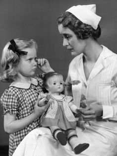 Nurse Consoling Young Girl and Her Doll Photographic Print