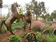 Perched alongside a pair of playful metal horse sculptures, wagon wheels give this garden a Wild West mien that escapes clichés.