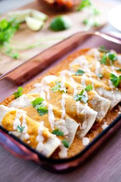 Vegan, gluten free enchiladas filled with roasted winter vegetables and topped with a creamy, dairy free pumpkin enchilada sauce, cashew crema and cilantro.