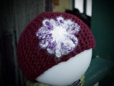 This is a hand made skull cap with a handmade purple and white flower on it. This cap was made with love and yarn. Size Medium.       (All skully caps run a little small)