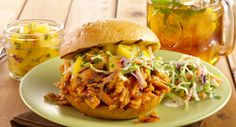Fork-tender chicken in a homemade barbecue sauce is piled onto a crusty roll and topped with a fresh peach salsa...