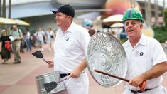 Two members of percussionist group JAMMitors pound on a pot and trashcan lid in Epcot