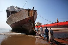 Workers climbing onto a ship at the Gaddani ship-breaking yard in Pakistan. The...