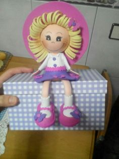 muñequita en fomy sentadita en una caja