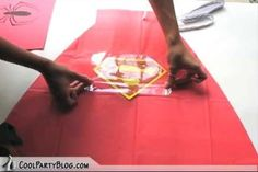 """In this tutorial, we learn how to create super hero cape party favors. First, take a plastic red table cover and remove it from the package. Next, open it up and fold it in half twice, so you end up with a rectangle. Then, take scissors and cut a large triangle shape out of the material. When finished, open up the cover and it will be in the shape of a cape! Then, cut out some """"s"""" for Superman signs and tape it on the back of the cape. Then, tie string around the top so it can be worn and…"""