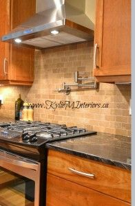 New Kitchen Design.  Natural cherry cabinets, dark black and gold flecked granite, travertine tile backsplash and Lenox Tan on the walls.  Beautiful island layout with small raised bar area for stools and prep sink.