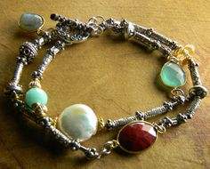 Bohemian bracelet with ruby, Peruvian green opal, citrine, labradorite, fresh water pearl and chalcedony in a two strand design. These lovely gems are accented with gold filled and gold vermeil beads and gold plated bezels. The strands are intermittent Thai Hill Tribe silver and Sterling silver beads with Sterling rings attaching the segments. The tiny 3mm Thai silver tube beads are textured in a tribal sun pattern; their color and patina blend so well with the gold filled and gold vermeil…