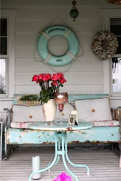 Diggin this beachy porch with distress blue glider and lifer-ring. I'd loose the shell wreath and just let it be. I have that glider and table. Need to refinish them and get them on my porch. Seaside Style, Beach Cottage Style, Beach Cottage Decor, Lake Cottage, Coastal Cottage, Coastal Decor, Cottage Porch, Coastal Living, Cottage Exterior