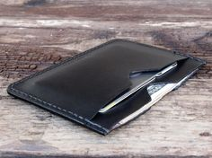 Black leather flat wallet by Tagsmith.