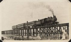 "Interurban train crossing temporary trestle built after the causeway was destroyed by the hurricane. From scrapbook: ""Interurban train crossing temporary trestle (No overhead, so locomotive is pulling trailers, motor and baggage cars)"". Galveston 1915 Hurricane Photographs, 1915. Special Collections, University of Houston Libraries (Public Domain)."
