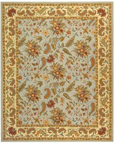 This beautiful transitional floral wool rug makes a colorful addition to any space. It is hand-hooked and features vibrant shades of light blue, green, red, and gold. Its fringeless border gives it a polished look. It is a soft yet durable rug.