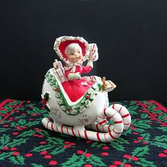 Here is the ceramic Holt Howard shopper girl in candy cane sleigh made by Lefton during the 1950s. There is still a Japan label on the bottom. It is in very good used vintage condition with no chips or cracks. The little shopper girl measures approximately 5 inches long, 5 1/4 inches high and 2 1/2 inches wide. She has the famous spaghetti trim on her hood. She is a great example of Christmas past.