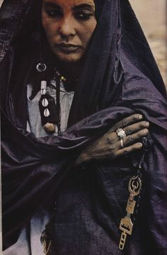 nationalgeographicscans:  Algeria, August 1973  Hands gleaming darkly with the indigo dye that colours her robe, a woman of the Tuareg- wandering Berbers of the Sahara- clasps her traditions close. The incised brass key marks her as guardian of the family's saddlebags.
