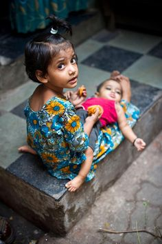 letswakeupworld:  A girl looks after her younger sister in Dharavi, a slum of Mumbai, India.