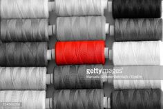 Stock Photo : Red Sewing Thread Stands Out From Grey Ones