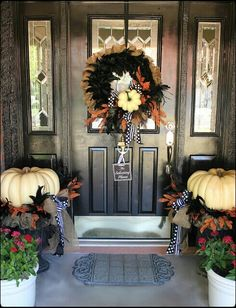 Fall/Halloween front porch/door ideas.  Inspiration.  White pumpkins tucked inside burlap wreaths in planters that match the wreath on the door...pretty.