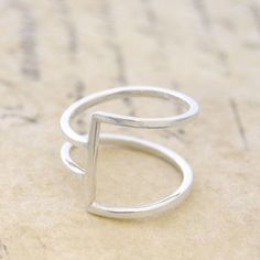 Simple and stylish, this geometric ring is handcrafted with sterling silver wire creating a contemporary, on-trend piece! Modern and abstract with a designer edge. #Otisjaxon #Jewellery #Accessories