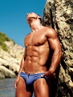 Bronzed muscle man in a li'l skimpy blue swimwear.