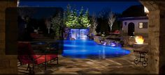 Residential swimming pool design - hand cut flagstone patio, beach entry, multiple waterfalls and large fire pit/conversation area - Perfect outdoor entertainment area!