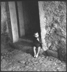 """FOTOGRAFIA_KATI_HORNA,Fot.33  """"Niño de Vicién""""    1937 04    Niño sentado en un peldaño de la puerta de su casa en Vicién (Huesca, España). Tiene su dedo índice en la boca.    60 x 60mm   Neg. Nitrato de celulosa. B/N    Fotografía publicada en la portada del periodico Umbral nº 24. 29 de enero de 1938"""